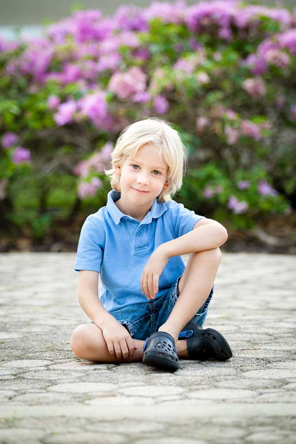 Boy sitting in front of flowering bushes