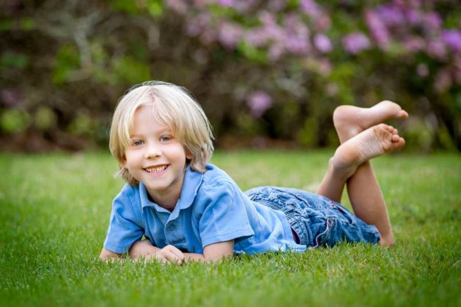 Boy laying relaxed in grass