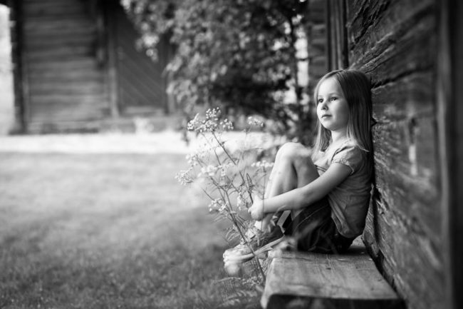Girl sitting against timber wall