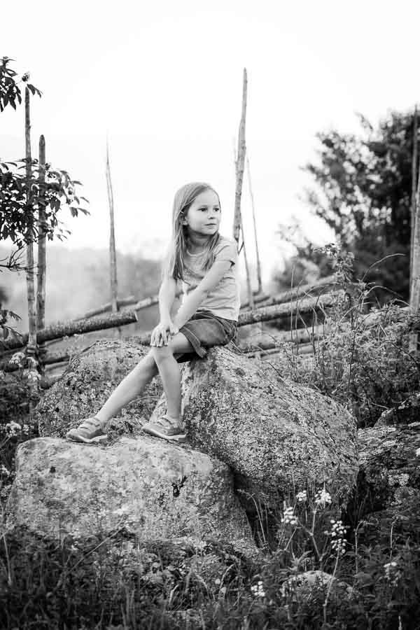 Girl sitting on pile of large rocks