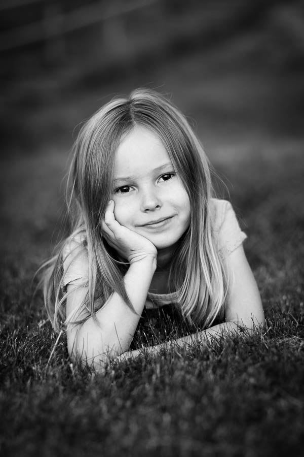 Girl laying on grass in black and white