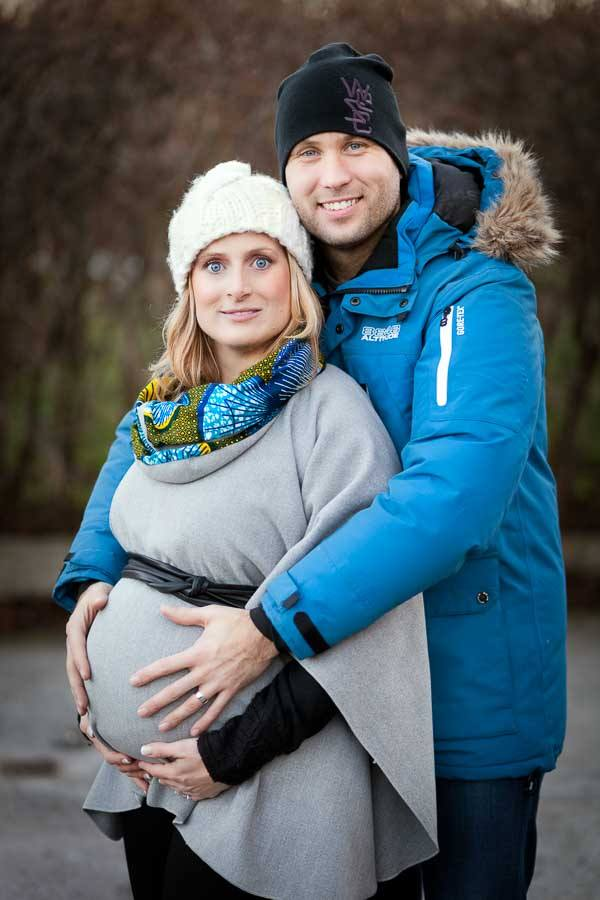 Maternity photo with couple holding hands on belly