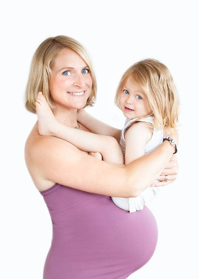 Girl siting on pregnant mum's belly