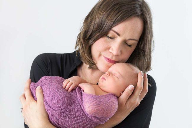 Mother cuddling newborn baby