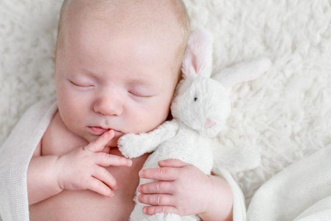 Newborn sleeping with cute fluffy bunny