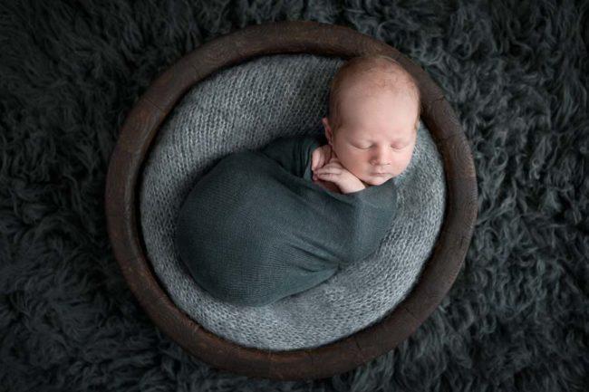 Newborn in bowl on grey floakti