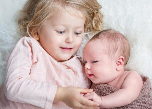 Newborn baby connecting with big sister